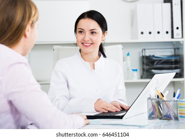 Smiling woman nurse arranging appointment for patient in hospital
