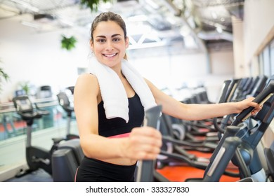 Smiling woman on the cross trainer at the gym