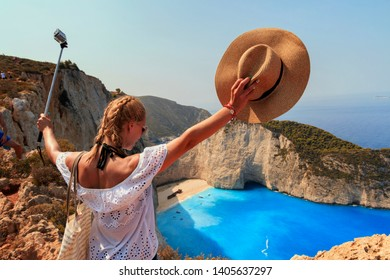 Smiling woman on holidays taking selfie over Zakynthos island Zante