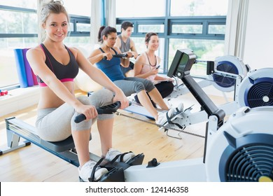 Smiling woman on rowing machine with others in fitness studio