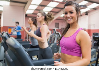 Smiling woman on a treadmill in the gym with other people