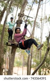 Smiling woman on zipline in adventure park