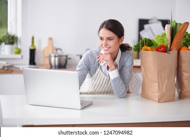 Smiling woman online shopping using computer and credit card in kitchen