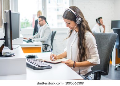 Smiling woman operator agent with headset taking notes while talking with client in call center