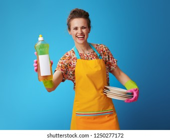 smiling woman in orange apron with washed plates and dishwashing detergent on blue background. Woman in orange-green protective gloves showing bottle of dishwashing detergent with a blank label