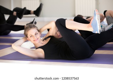 Smiling woman with other people doing abs crunches lying on rubber mats at gym. Millennial girls guys wearing sportswear do stomach situp exercises. Wellbeing wellness and sportive lifestyle concept