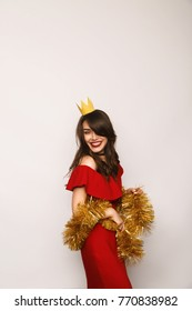 Smiling woman with paper crown and golden tinsel posing and looking at camera.