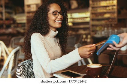 Smiling woman paying contactless using her credit card in a cafe to pay her bill. Female customer making a card payment in a restaurant.