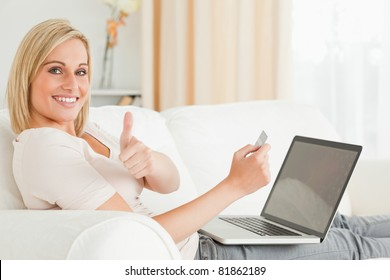Smiling woman paying her bills on line with her thumb up