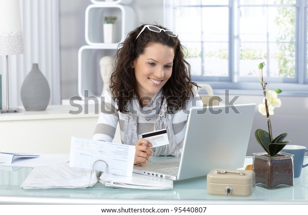 Smiling woman paying online for purchase with creditcard, using laptop computer.?