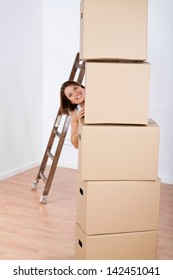 Smiling woman peering from behind stacked plain brown cardboard boxes when moving house to a new location