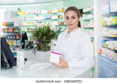 Smiling woman pharmacist is standing welcoming near cashbox in pharmacy
