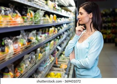 Smiling woman picking vegetables in supermarket