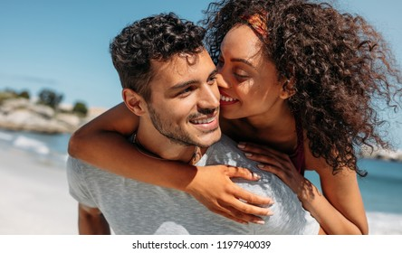Smiling woman piggy riding on her boyfriend and kissing him. Man carrying his girlfriend on his back outdoors.