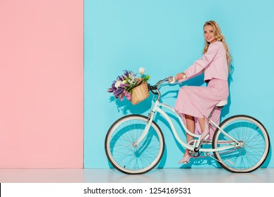 smiling woman in pink clothing riding bicycle with flower basket on pink and blue background