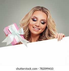 Smiling Woman with Pink Gift BoÑ? and White Paper Banner Background