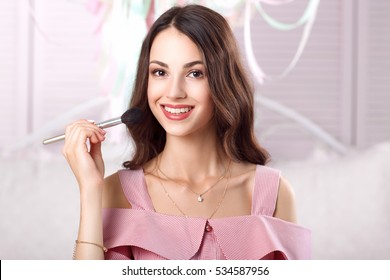 Smiling woman in pink powdering her face with brush. Attractive girl doing makeup, applying roygemon face. Makeup, fashion, cosmetics, female accessories concept