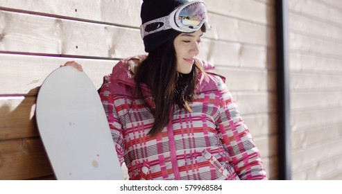 Smiling woman in pink snowsuit with board