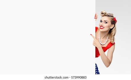 Smiling woman in pin-up style dress, showing blank signboard with copyspace, on grey background. Caucasian blond model posing in retro fashion and vintage concept studio shoot. Banner composition.
