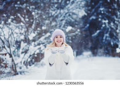 Smiling woman playing with snow in park