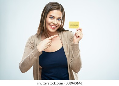 Smiling woman pointing finger on credit card. White isolated portrait.