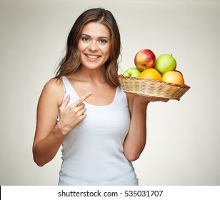 smiling woman pointing finger on apple. isolated portrait of beautiful girl with long hair holding basket with apples.