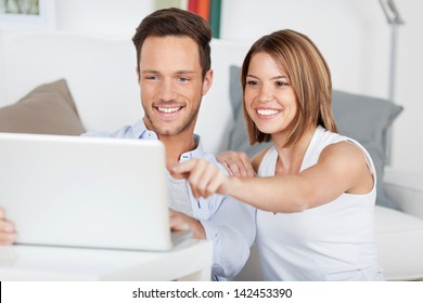Smiling woman pointing something at the laptop