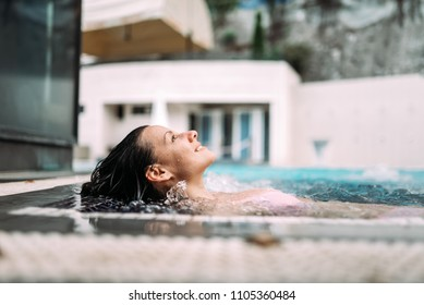 Smiling woman in the pool at spa resort.