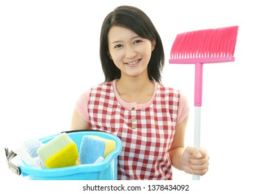 Smiling woman posing with cleaning supplies.