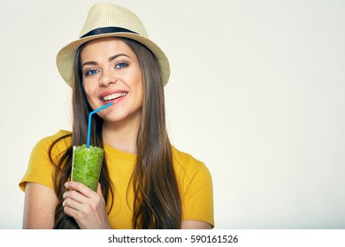 Smiling woman preparing green smoothie in blender. Isolated studio portrait.