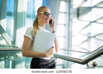 Smiling woman professional jurist in formal wear and paper documents in hand having pleasant mobile phone conversation while standing in contemporary company corridor. Cheerful female CEO phoning
