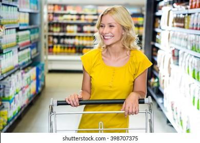 Smiling woman pushing cart in supermarket