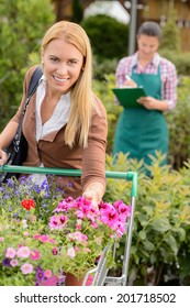 Smiling woman put flowers in shopping cart in garden center