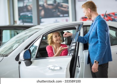 smiling woman receives the keys to a new car from a sales manager
