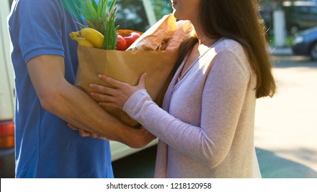 Smiling woman receiving grocery bag from delivery worker, supermarket service