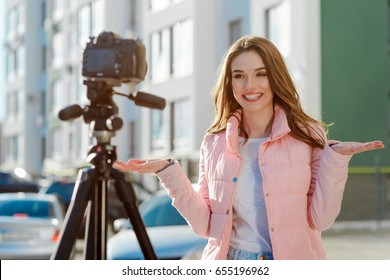 Smiling woman recording a video outdoors. Blogger using a camcorder on a tripod to make a video about new apartment house.