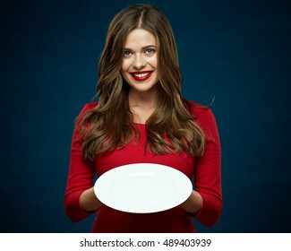 smiling woman in red dress holding white empty plate