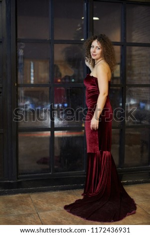 Smiling woman in red dress stands half-turned near latticed window in  evening room. 75cd8e1d5