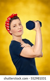 Smiling woman with red kerchief and blue t-shirt lifting a weight in front of yellow background, tribute to american worker icon Rosie the Riveter, sign for women power