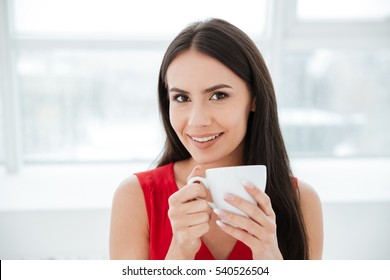 Smiling woman in red shirt holding cup of tea in office and looking at camera. Window on background