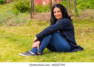Smiling woman rests on grass in countryside garden