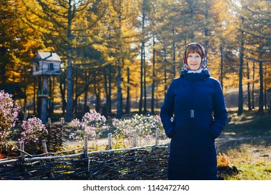 smiling woman of retirement age in autumn coat looking at camera, yellow leaves