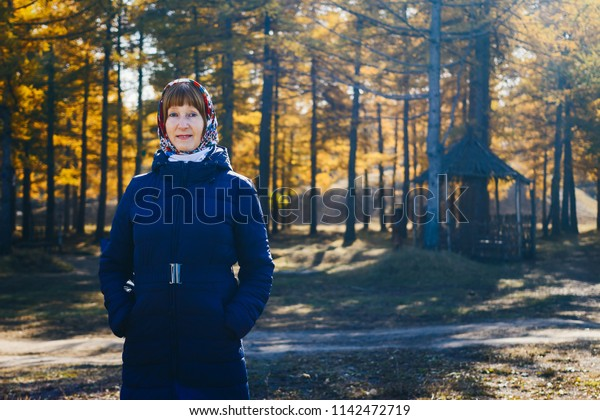 smiling woman of retirement age in autumn coat, yellow leaves