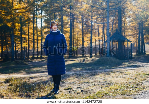 smiling woman of retirement age in full length in autumn coat