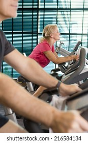 Smiling woman riding exercise bike in health club