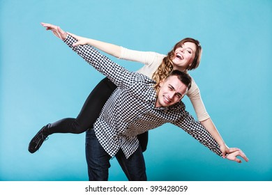 Smiling woman riding piggyback on man shoulders. Happy young couple having fun together in studio on blue.