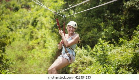 Smiling woman riding a zip line in a lush tropical forest