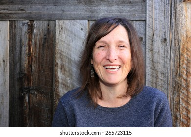 Smiling woman with a rustic wood background.