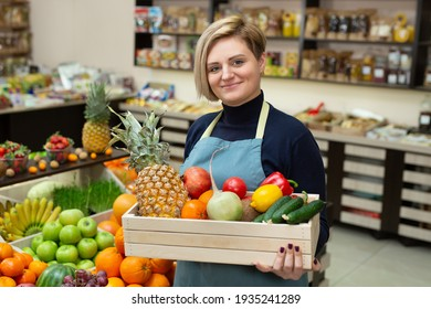 Smiling woman salesman holds a wooden box with vegetables and fruits in the store.