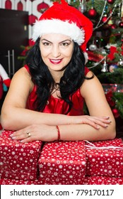 Smiling woman with santa hat resting hands on many Christmas gifts
